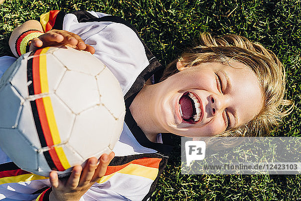 Boy in German soccer shirt lying on grass  laughing happily