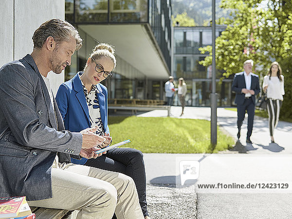 Colleagues with tablet sitting on bench outside office building