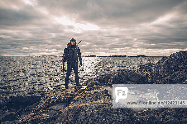 Sweden  Sodermanland  backpacker standing at the seashore under cloudy sky