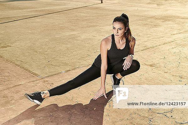Sportive woman stretching leg on concrete floor