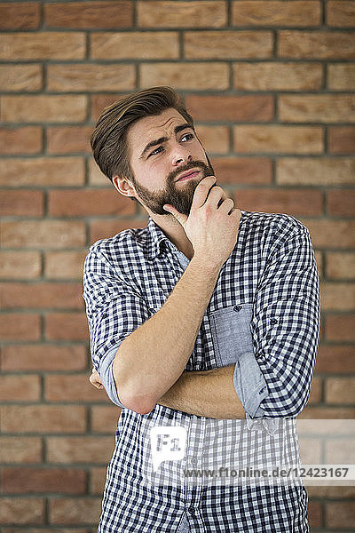 Portrait of bearded young man in front of brick wall thinking