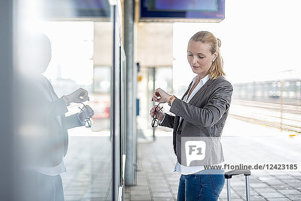 Mature businesswoman standing at platform checking the ime