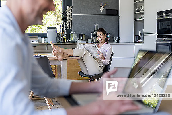 Couple at home with man using a laptop and woman reading newspaper