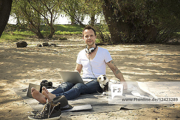 Portrait of man with dog sitting on blanket at a beach using laptop