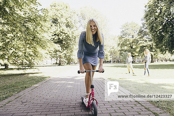 Happy young woman riding scooter in a park