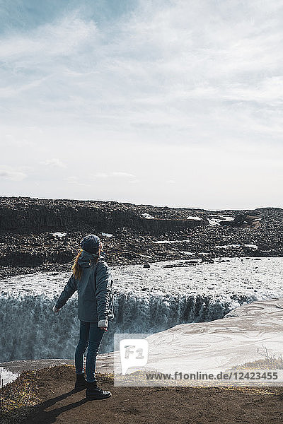 Iceland  woman standing at Dettifoss waterfall