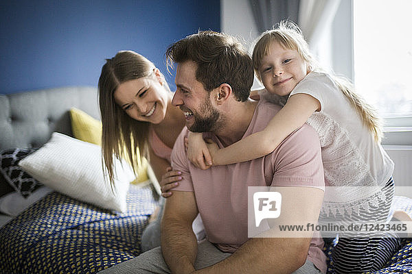 Happy family lsitting on bed  embracing