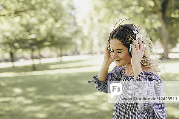 Smiling young woman in a park enjoying listening to music with headphones