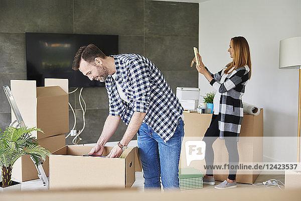 Couple moving into new flat unpacking cardboard box Couple moving into new flat unpacking cardboard box