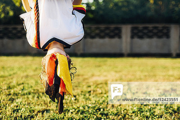 Boy in German football shirt  hanging upside down with face covered by German flag