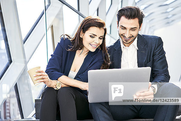 Smiling businesswoman and businessman sharing laptop on stairs in modern office