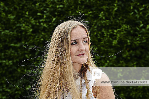 Blond young woman at a hedge looking sideways