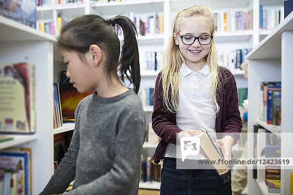 Two schoolgirls in school library