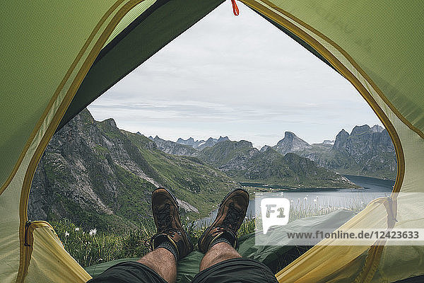 Norway  Lofoten  Moskenesoy  Feet of man  lying in a tent over Kjerkefjord