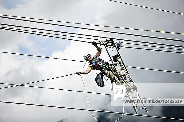 Fitter with ladder  pulling along high-voltage power line