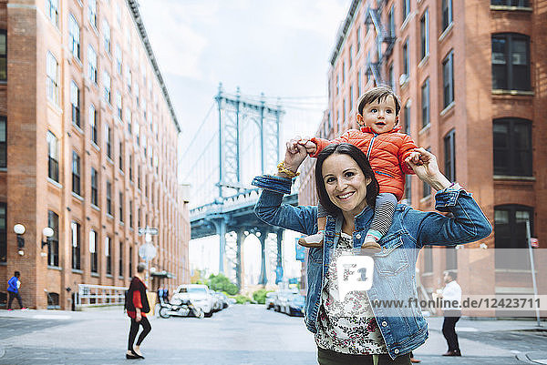 USA  New York  New York City  Mother and baby in Brooklyn with Manhattan Bridge in the background