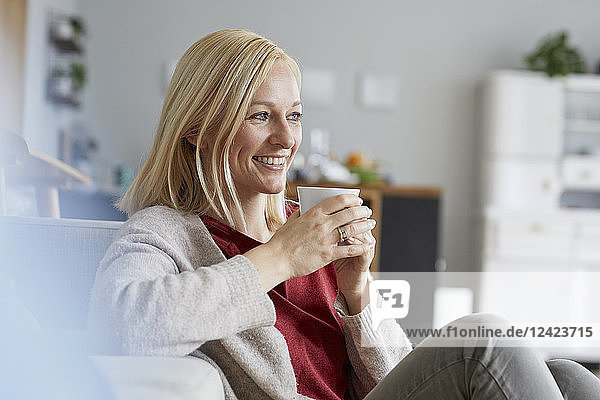 Happy woman relaxing at home  drinking coffee