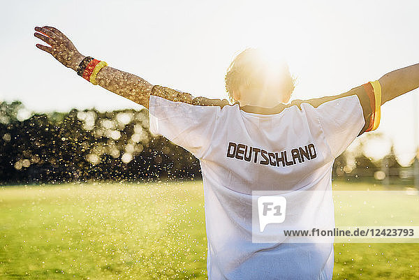 Cheering boy wearing football shirt with Germany written on back