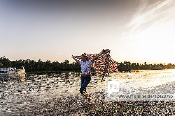 Young woman walking barefoot on riverside with blanket