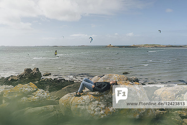 France  Brittany  Landeda  young woman wearing headphones lying on rock at the coast