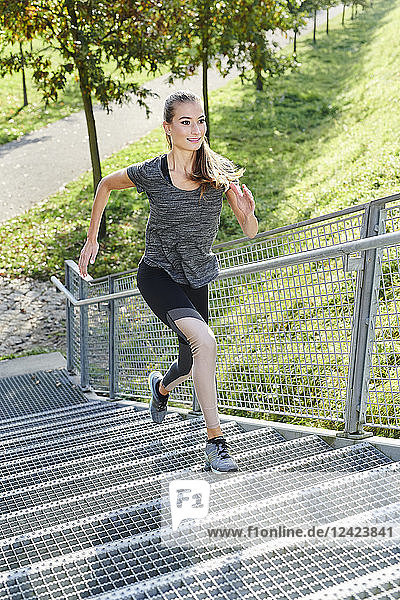Young woman running on stairs in a park
