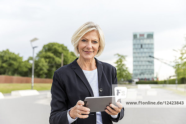 Portrait of confident senior businesswoman with tablet outdoors