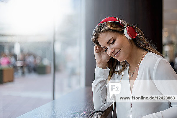 Smiling young woman listening to music with headphones