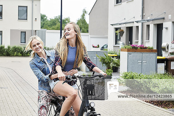 Two happy young women riding bicycle together on one bike