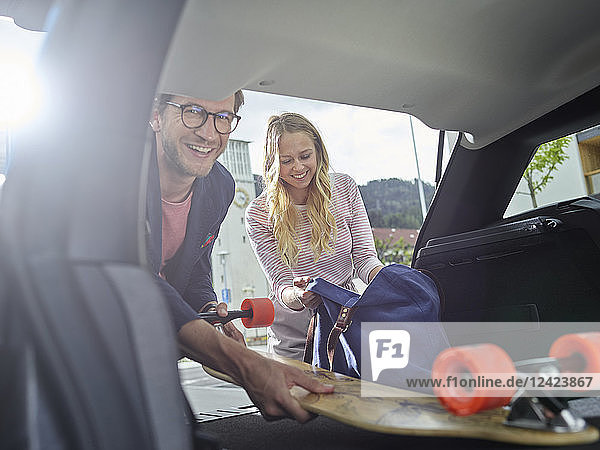Smiling couple loading boot of electric car
