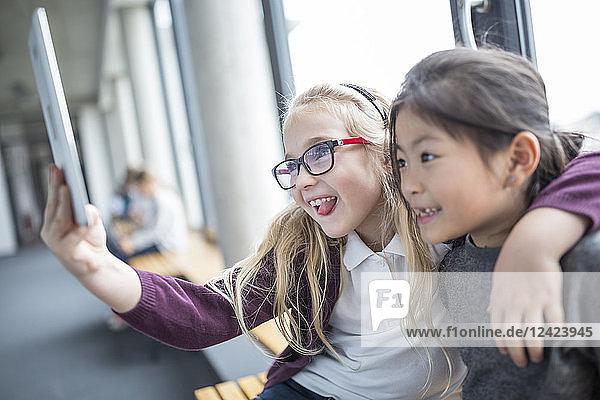 Happy schoolgirls taking a selfie with tablet on school corridor