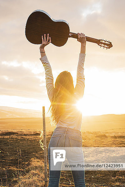 Iceland  woman with guitar at sunset