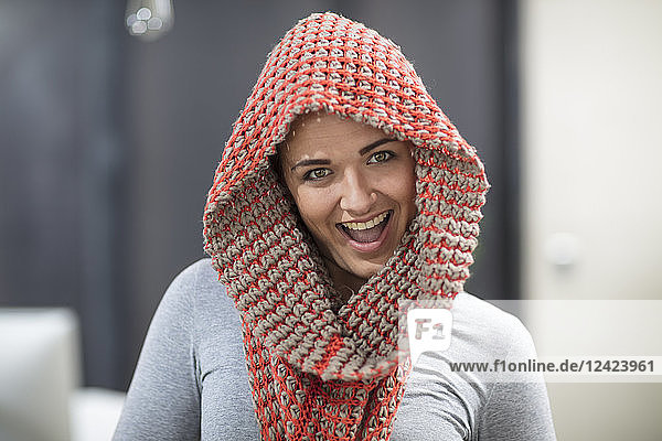 Portrait of happy young woman wearing scarf in office