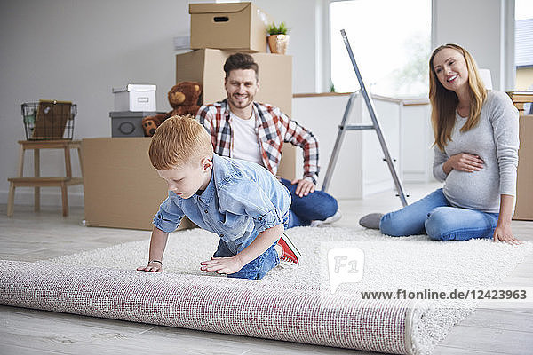 Boy with parents unrolling a carpet in new flat