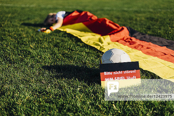 Boy sleeping under German flag with do not disturb sign due to soccer world championship