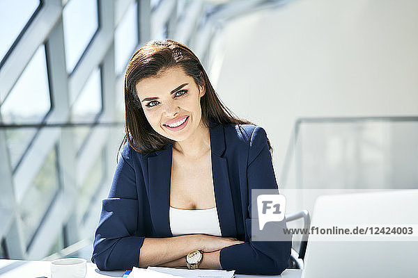 Portrait of smiling businesswoman sitting at desk in modern office
