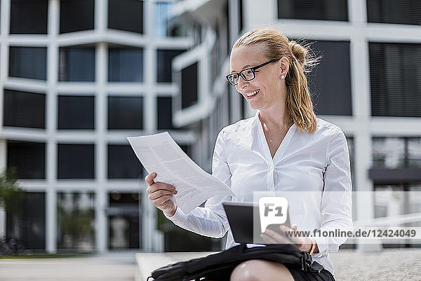 Portrait of smiling businesswoman with documents and tablet sitting in front of office building