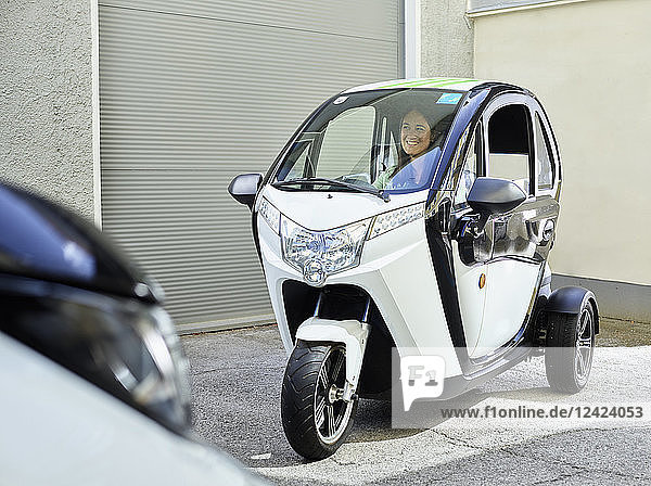 Smiling woman sitting in electric bubble car
