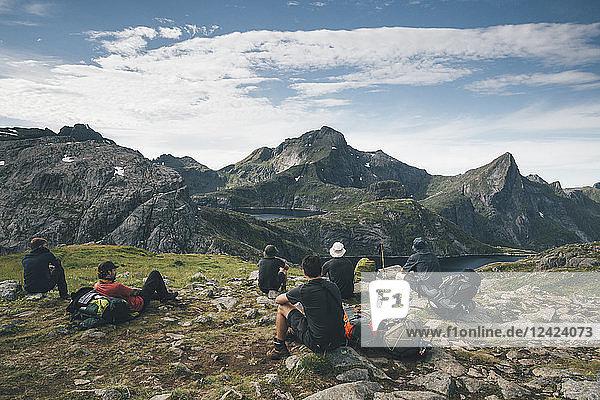 Norway  Lofoten  Moskenesoy  Young men taking a break  looking at the mountains