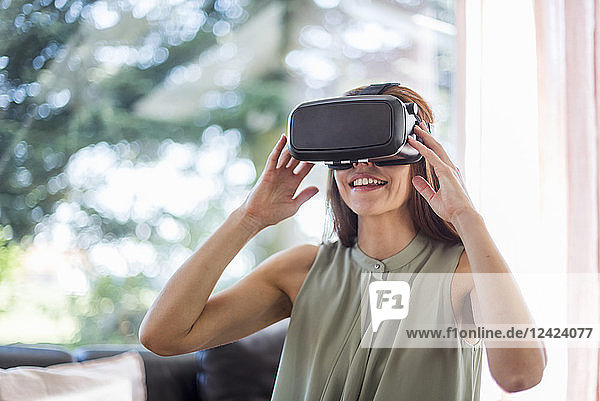 Smiling woman at home wearing VR glasses