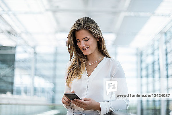 Smiling young woman standing at railing using cell phone