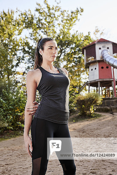 Sportive woman stretching arm in park