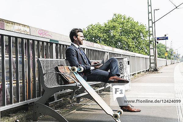 Smiling businessman with skateboard using laptop at the platform
