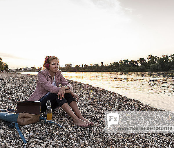 Young blond woman with earphones and tablet on riverside in the evening