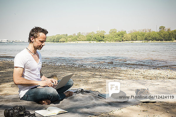 Man sitting on blanket at a river using laptop