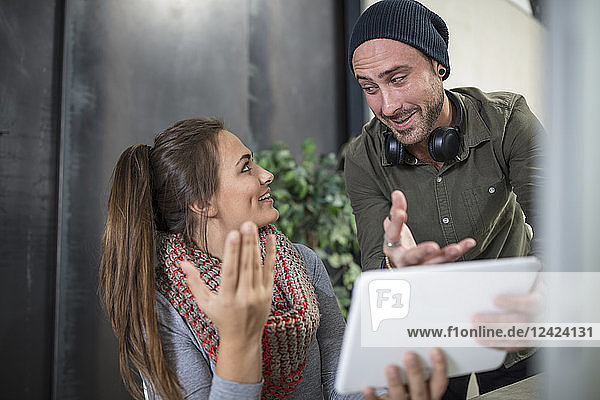 Two colleagues with tablet talking in office