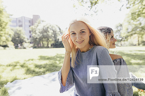 Portrait of two smiling young women relaxing in a park