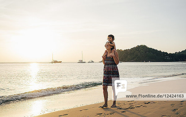 Thailand  Krabi  Koh Lanta  Mother with little daughter on her shoulders on the beach at sunset