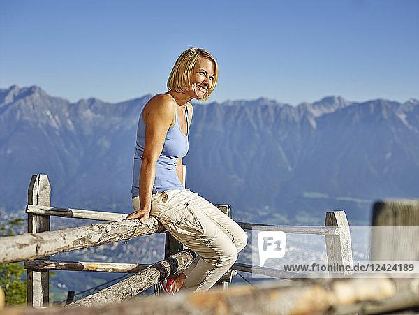 Austria  Tyrol  Hiking woman sitting on fence  taking a break