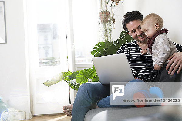 father sitting on couch with his little daughter  using laptop