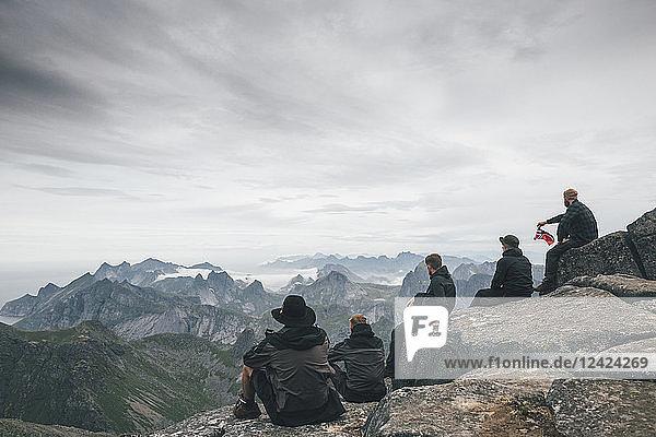 Norway  Lofoten  Moskenesoy  Young men sitting at Hermannsdalstinden  looking over Kjerkefjord